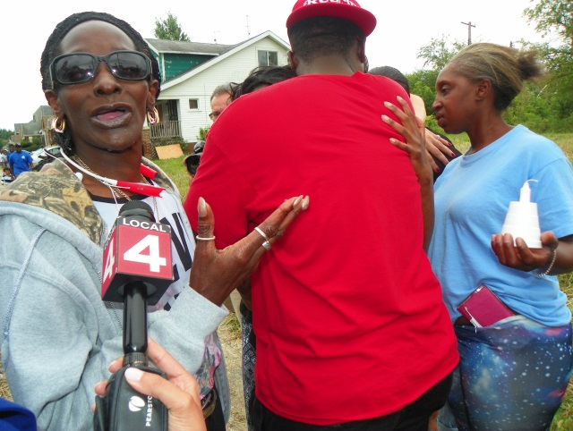 Children's great-grandmother Marie Jackson speaks to news at vigil as neighbor hugs children's mother Alisha Jackson.