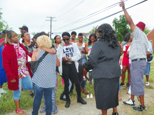 Family, neighbors console Alisha Jackson, being hugged by woman in blue-checked shirt, at vigil.