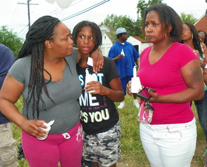 Mother holds child tightly during candlelight vigil June 26 at Jackson family home.