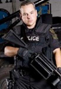 Joseph Weekley in SWAT uniform with gun