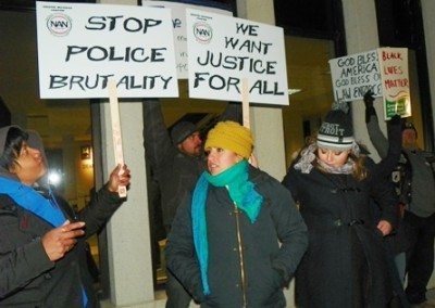 Protesters directly in front of Dearborn Police station block signs of pro-police supporters.
