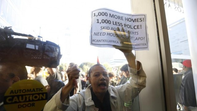 Protester demands homes, not police.