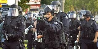 LAPD cops advance in battle gear.