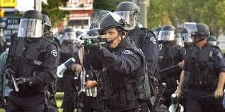 LAPD cops advance in battle gear.
