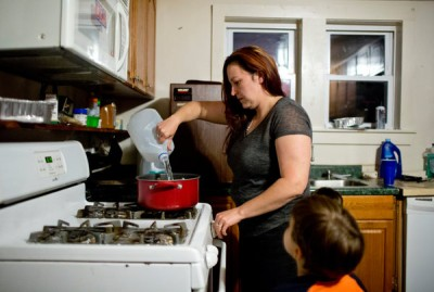 LeeAnne Walters, watched by her son Garrett, uses bottled water to make pasta because her tap water is often brown. She said Garrett's twin, Gavin, 4, had lost weight and tested for elevated lead levels since Flint switched water sources. Photo: LAURA MCDERMOTT FOR THE NEW YORK TIMES