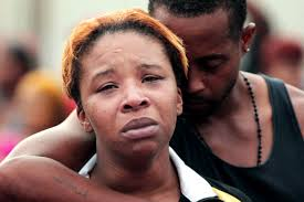 Mike Brown's mother Lesley McSpadden is comforted by her husband, Louis Head, the day her son was killed.