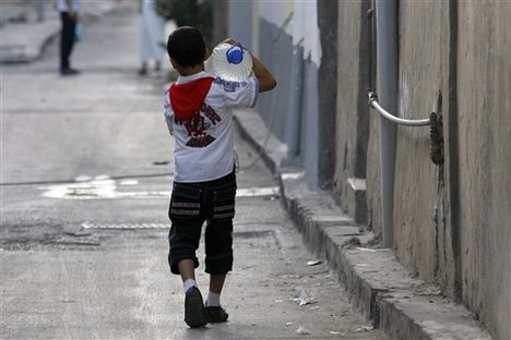 Libyan child carries jug of water after U.S./CIA bombing of his country under the Obama administration destroyed its world-class water infrastructure.