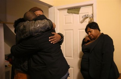 Melvin Jones, facing camera, hugs Robin Andrews, both brothers of Bettie Jones, 55, in Jones' living room after she was shot and killed by a Chicago police officer.