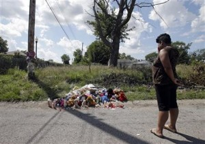 Woman stops by memorial for Andre Green, 15, in Indianapolis alley where he was killed by police.