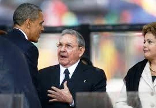 U.S. Pres. Barack Obama and Cuban President Raul Castro shook hands at Dec. 2013 memorial for Nelson Mandela. Brazililan President Dima Roussef watched.