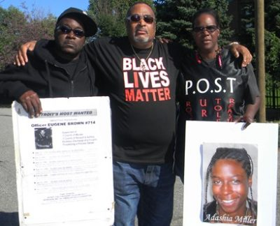 Kevin Kellom, Pastor Jerome McCorry, and Yolanda McNair, leader of P.O.S.T., holding poster with her daughter Adaisha Miller's photo.
