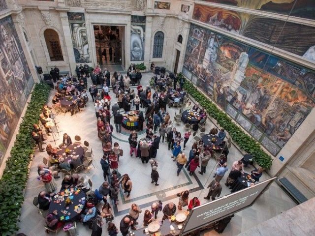 Wealthy partygoers celebrate opening of Frieda Kahlo-Diego Rivera art display in courtyard. Ironically, they partied in front of Rivera's mural celebrating Detroit workers and representing his Communist beliefs.