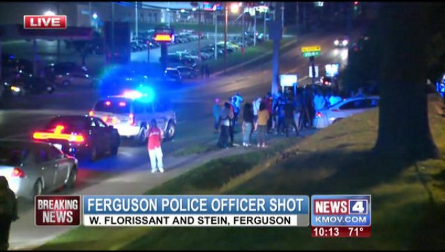 Ferguson police set up a staging area near scene of Mike Brown's shooting after cop shot; the cop was shot over 2 miles away at the Ferguson Community Center. Confrontations between bystanders and police resulted at this scene.