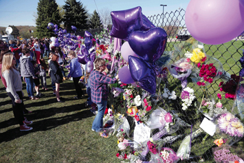 A memorial fence in memory of pop star Prince is lined with flowers and signs at Paisley Park Studios, April 22, in Chanhassen, Minn. Prince died April 21 at Paisley Park at the age of 57.