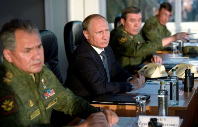 Russian Pres. Vladimir Putin flanked by military leaders.