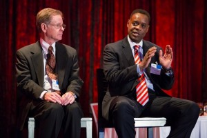 Orr holds forth at Crain's Newsmakers luncheon as Rhodes listens.