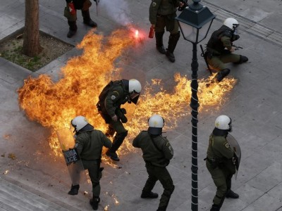 Riot police in Athens duck petrol bomb thrown by protesters Feb. 4, 2016