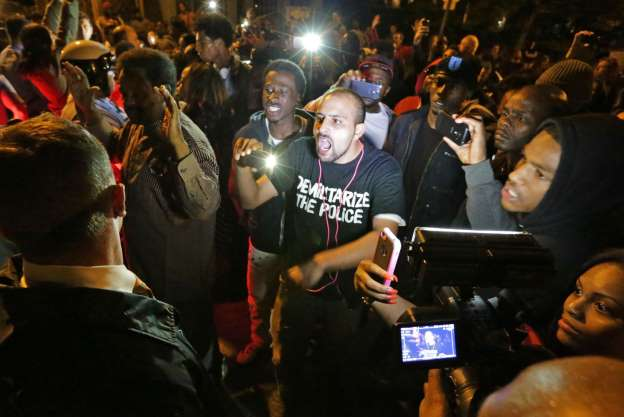 Angry crowd confronts St. Louis police after off-duty cops kills Black teen Oct. 8, 2014/AP