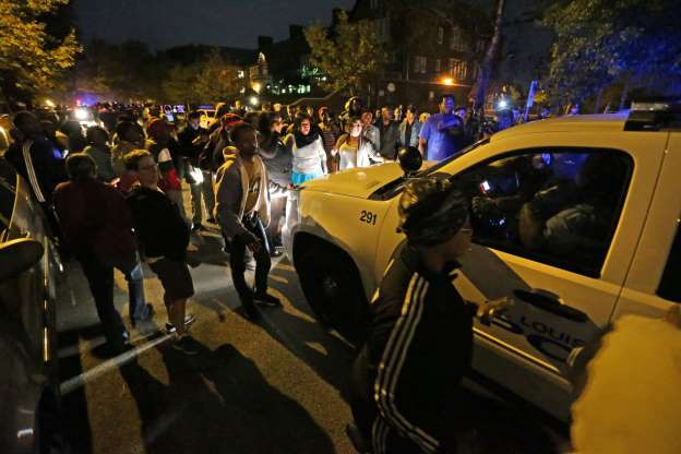 Crowd confronts police car in St. Louis; tweets later reported police car and truck windows were broken out.