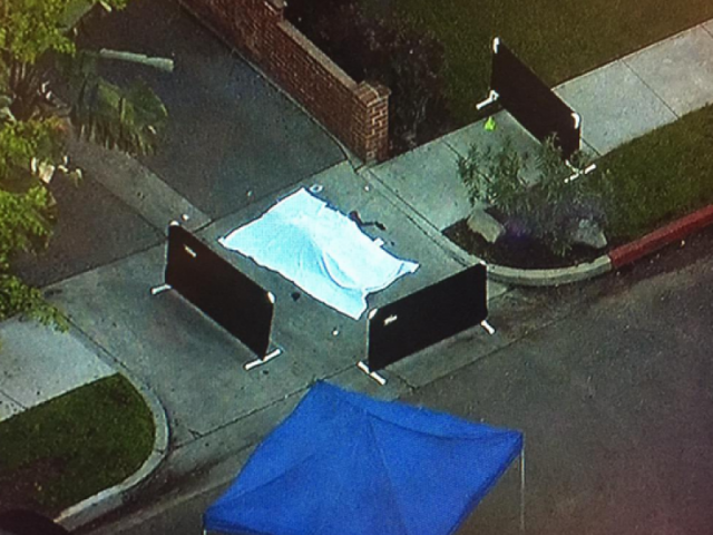 Body of Sergio Navas, 35, is under the white covering on street where he died.