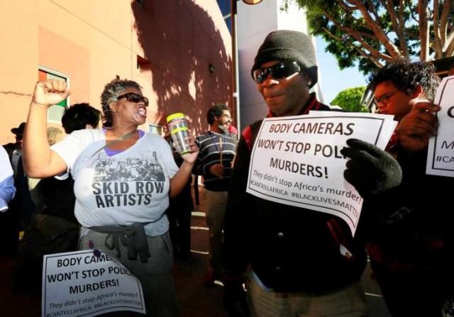 Suzetta Shaw, a homeless woman at left, joins other homeless protesters at site of Africa's slaughter by LAPD.