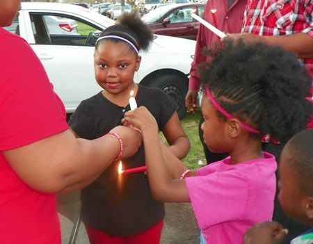 Children help each other light candles.