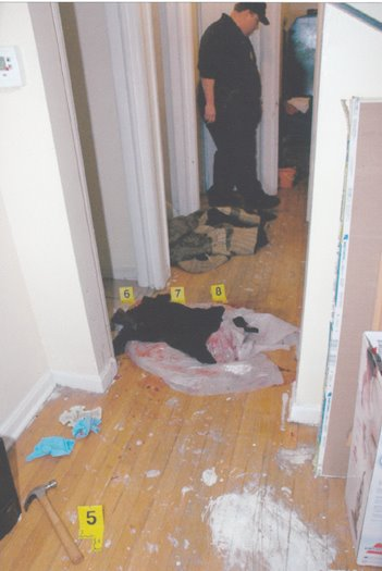 "Photo of hall after Kellom's killing. It is not time stamped. Black cloth and plastic wrap appear to cover most of blood at foot of stairs. It is unknown whether hammer at lower left was there when Kellom was killed, or was placed there by police afterwards, as they do with ""throw-away"" guns."