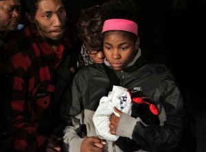 Tamir Rice's father Leonard Warner comforts the child's big sister at vigil in park where he was killed.)
