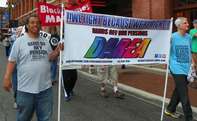Bill Davis, President of DAREA (l) carries banner at Wayne County tax foreclosure protest June 8, 2015.