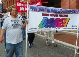 DAREA Pres. Bill Davis carries banner at tax foreclosure protest June 8, 2015.
