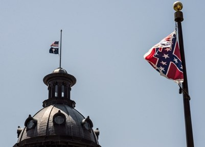 The South Carolina and U.S. flags fly at half staff at state capitol as the Confederate flag unfurls at full staff at the Confederate Monument nearby, in Columbia, SC. Sean RayfordGetty /Images