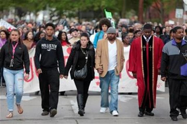 (M.P. King/Wisconsin State Journal via AP). Andrea Irwin, center, mother of Tony Robinson, and her boyfriend, Jeff Jackson, center right, participate in a protest march on Williamson Street, Tuesday, May 12, 2015, in Madison, Wis. Dane County District.