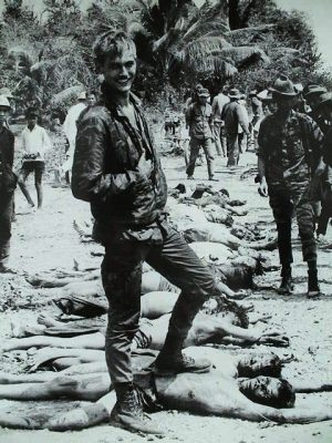 U.S. soldier grins over bodies of Vietnamese patriots killed defending their country.
