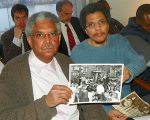 Detroit retiree Walter Knall, historian Paul Lee hold up photo depicting historic rally in Detroit during consent agreement hearings. Pugh ordered police to remove Lee from chambers.