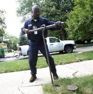 Homrich employee shuts water off to Detroit home.